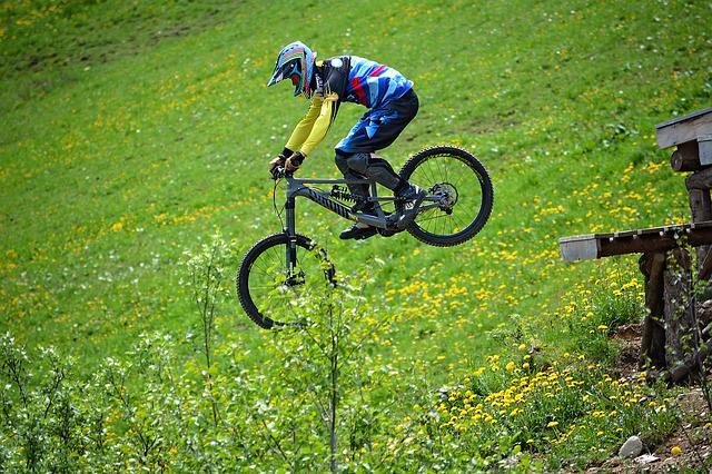 Chłopak jedzie na rowerze po trawie