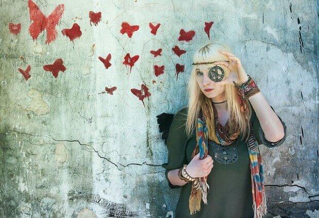hippiska stojąca na tle ściany pomalowanej w motyle