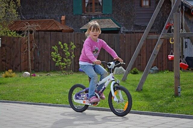 dziewczynka jeździ rowerem po podwórku