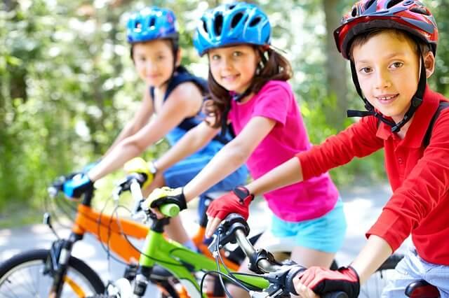 dzieci w kaskach jadące na rowerach