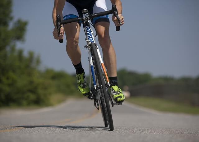 kolarz jadący na rowerze po szosie