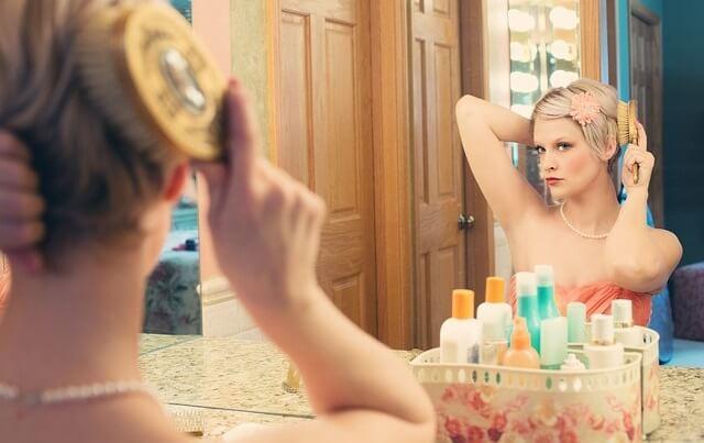 Kobieta szykująca się przed lustrem