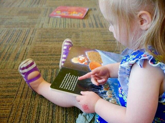 Dziewczynka uczy się czytać książeczkę