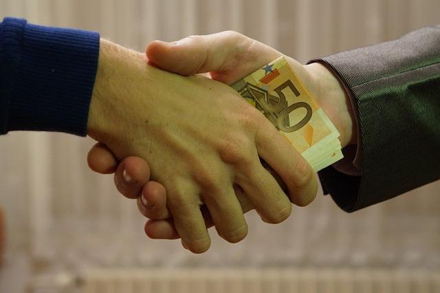Mężczyźni podający sobie pieniądze